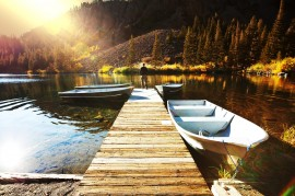 Autumn setting - a boat sits by a jetty by the lake